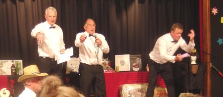 Les Clements (left) and Simon Muir (right) assist auctioneer Grant McIlroy (centre) raise funds at the recent Kirwee Casino night.