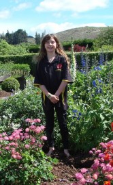 Poppy Freeman stands  amidst a wonderful floral display in the family garden.
