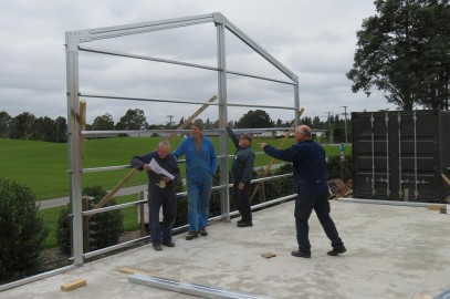 """First frame of the Woodwork Shed extension goes up"""". L to R: Arnold Tibbetts, Paul Hurrell, Ron Petersen & Colin Richardson."""