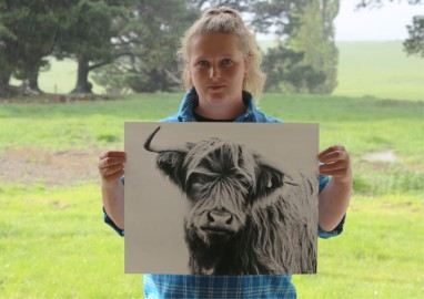 Georgia holding her most popular print 'Wonky Cow'.